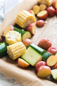 arranging corn, zucchini, and potatoes on a sheet pan for chicken
