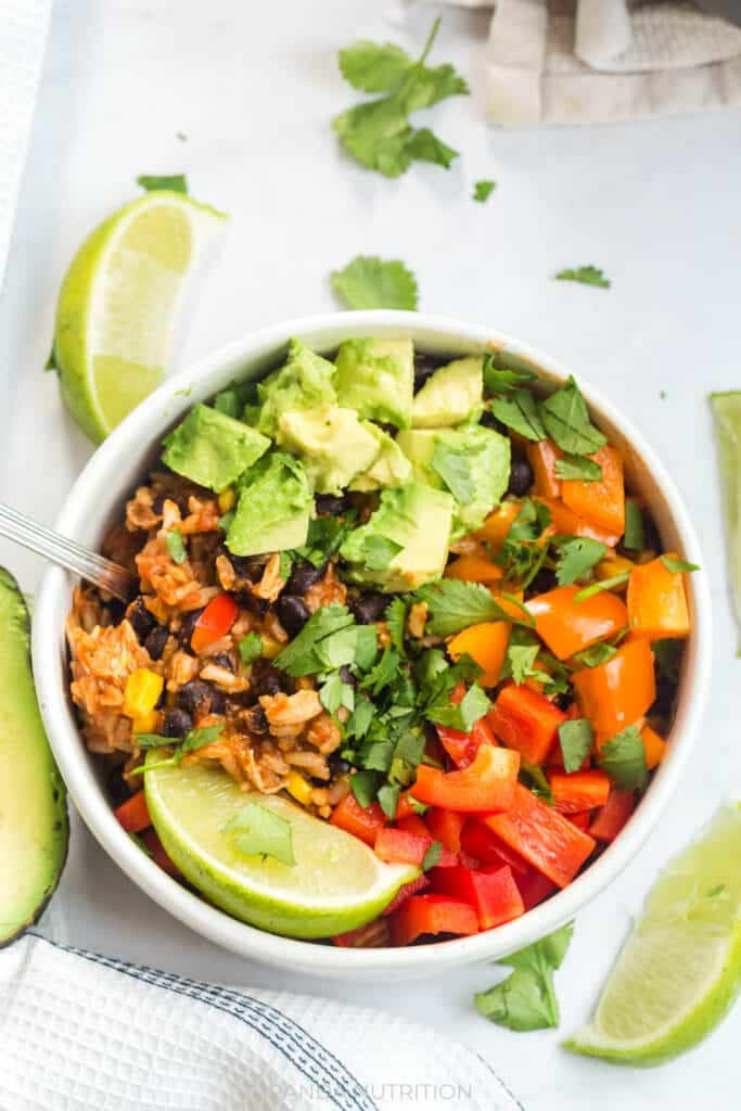 close up overhead view of a white bowl with fresh avocado, orange and red pepper, lime, and cilantro over a rice and chicken bowl