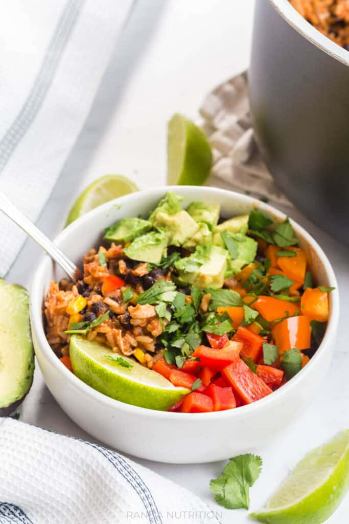 Chicken burrito bowls made in a Ninja Foodi, topped with cilantro, avocado, and raw bell peppers