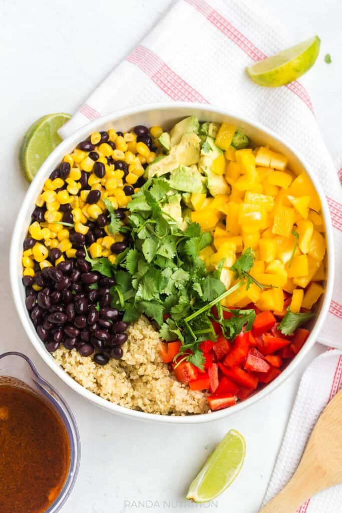 corn, black beans, cilantro, bell peppers, quinoa, avocado in a bowl for a summer salad