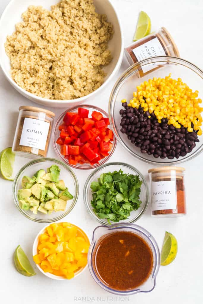 ingredients for mexican quinoa salad laid out with pretty spice jar labels