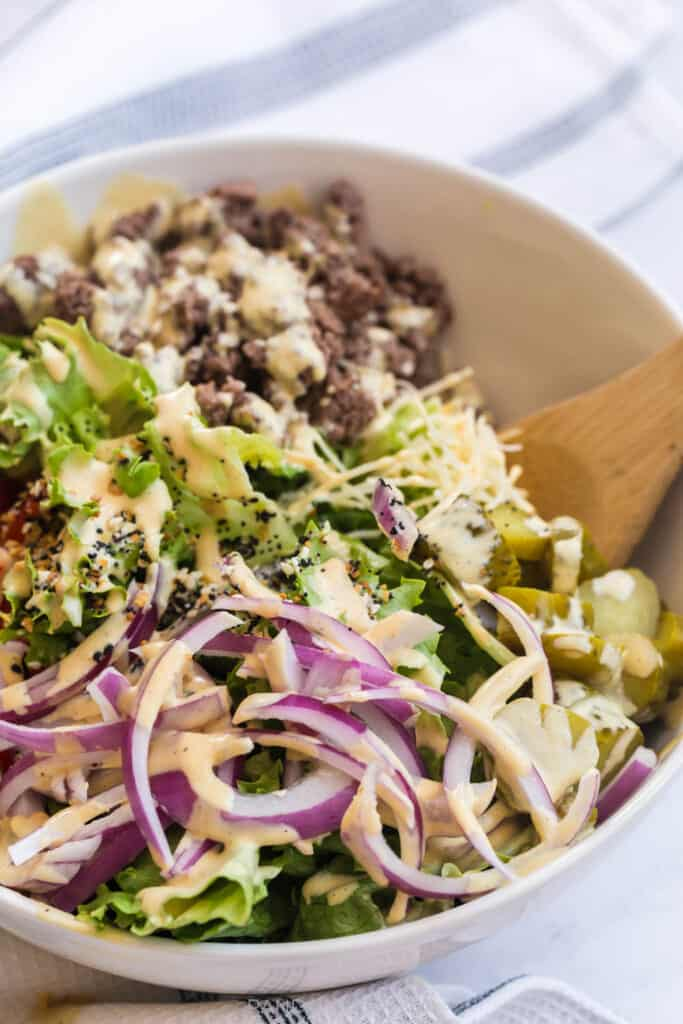 side shot of red onion with dressing on it in a burger bowl