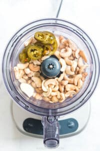 pickled jalapenos, cashews, lime juice, garlic in a food processor ready to make sauce