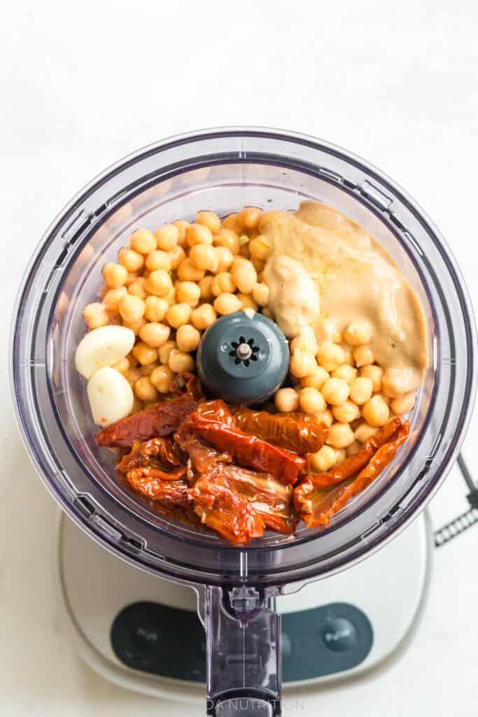 adding chickpeas, tahini, sun dried tomatoes, garlic, and lemon to a food processor