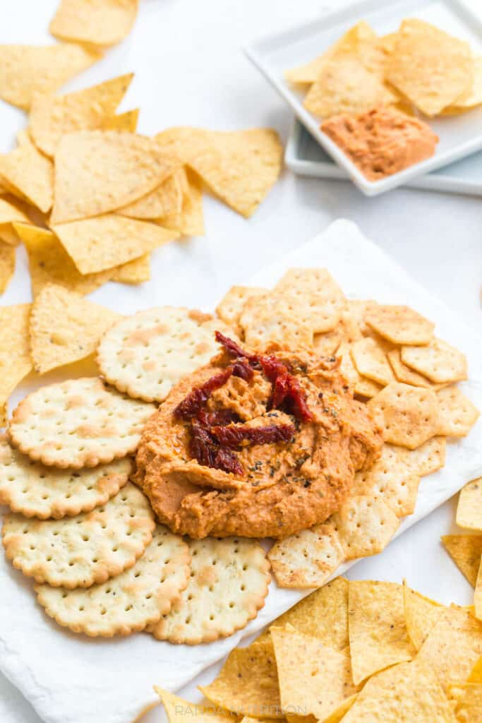 angle view of sun dried tomato hummus on a white slate platter surrounded my crackers for a party