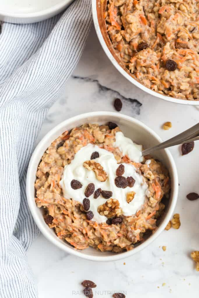 close up of oats with raisins, greek yogurt, and carrots with cinnamon