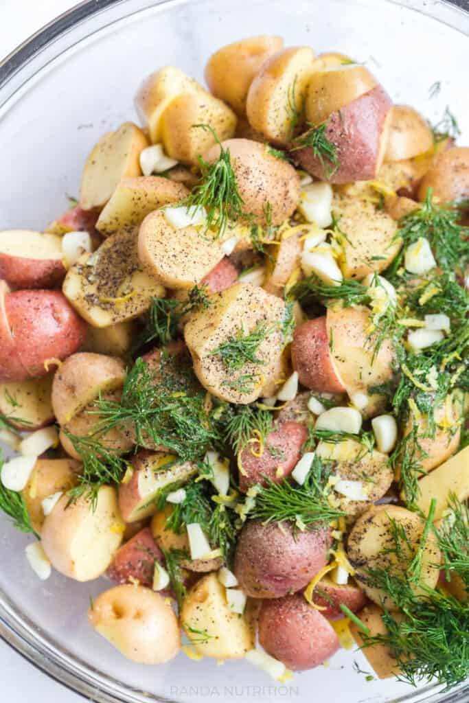 marinating potatoes with herbs and garlic before adding to a sheet pan