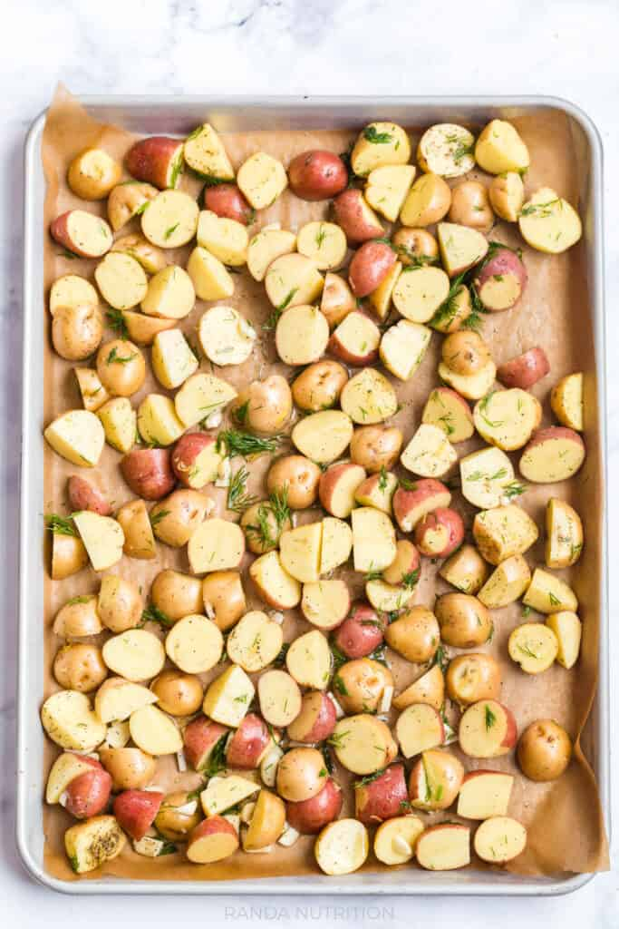 potatoes, garlic, dill weed, salt, pepper, and oil on a sheet pan