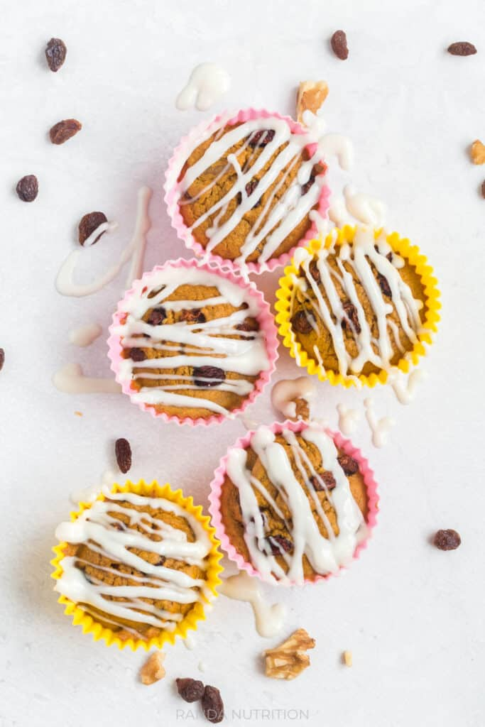 over top view of muffins with a greek yogurt drizzle and raisins