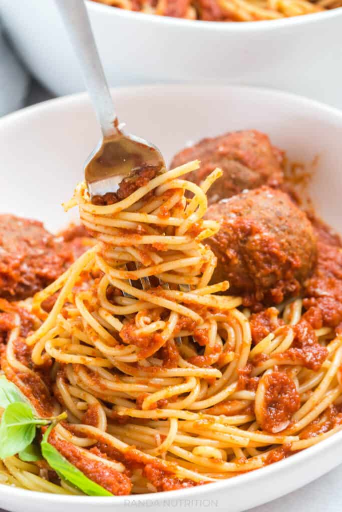 spaghetti being twirled with a fork with marinara sauce