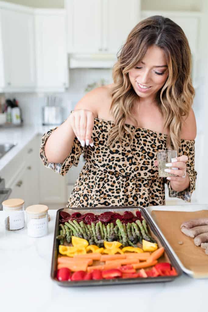 woman sprinkling seasoning over sheet pan vegetables