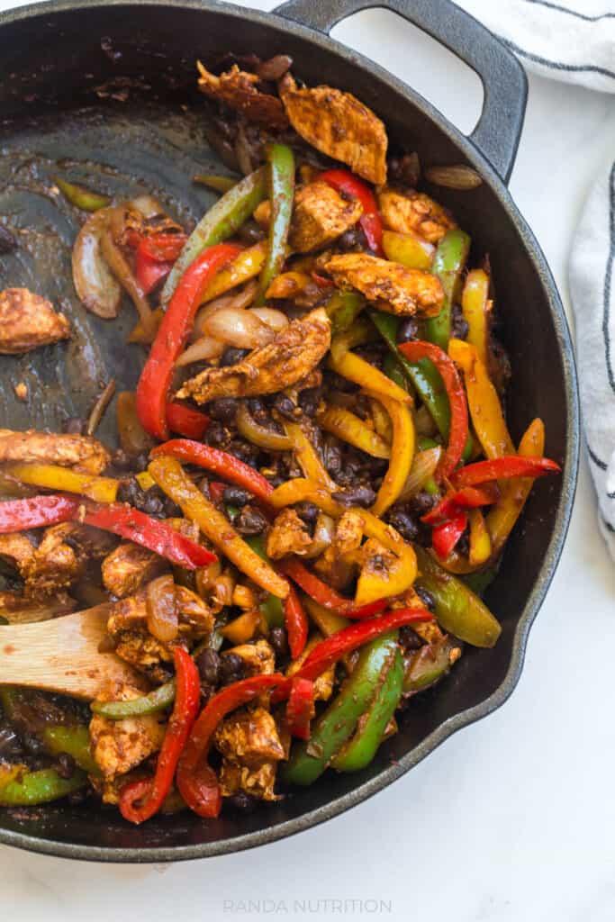 cast iron pan with cooked chicken fajita mixture