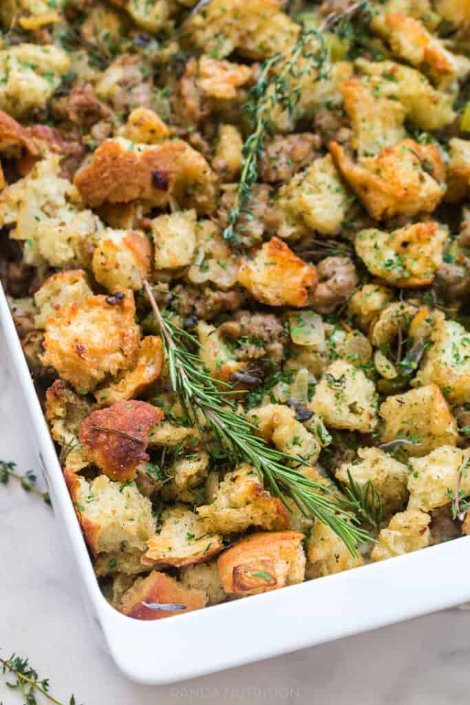 close up of homemade stuffing fresh out of the oven with rosemary and sage